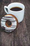 Cup of coffee and donut on the wooden desk. Cup of coffee and fresh donut on the wooden desk Stock Photos