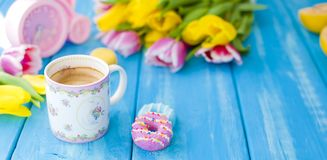 A cup of coffee and donuts on a blue wooden background. Bouquet of flowers yellow and pink. The pink clock is like a bicycle. stock images