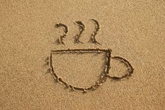 Cup of coffee is drawn on a sand beach on a sunset. royalty free stock photos