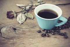 Cup of coffee with dried rose on old wooden table Royalty Free Stock Images