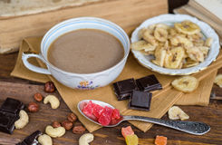 Cup of coffee with dry fruits and chocolate on napkin royalty free stock photo