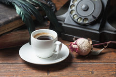 Cup of coffee, dry rose and old telephone Stock Images