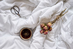 Cup of coffee, dry roses and vintage scissors on bed Royalty Free Stock Photo