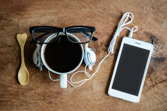 Cup of coffee with earphone and cellphone Royalty Free Stock Photo