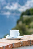 Cup of coffee on edge at sea view. Vertical view with white cup Royalty Free Stock Photography