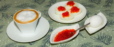 Cup of coffee. Egg with red caviar royalty free stock image