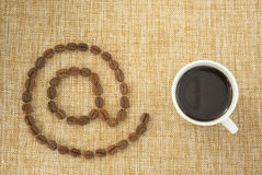 Cup of coffee and email sign. Stock Images