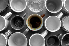 Cup of coffee between the empty cups Royalty Free Stock Image