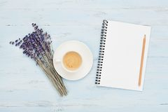 Cup of coffee, empty notebook and lavender flower on blue table top view. Woman working desk. Cozy breakfast. Flat lay style. Royalty Free Stock Photos
