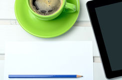 Cup of coffee with empty paper and tablet Stock Image