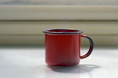 Red enamelled cup of coffee Royalty Free Stock Photo