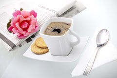 A cup of coffee enclose by a newspaper and a rose. A delicious cup of coffee with biscuits a newspaper and a rose ready for a perfect morning Stock Photos