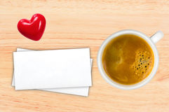 Cup of coffee and envelops on wooden table, top view Stock Image