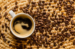 Cup with coffee and espresso beans on a woven serving tray. Cup with freshly made coffee and roasted espresso beans on a woven serving tray Stock Photos