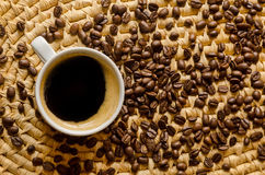 Cup with coffee and espresso beans on a woven tray. Cup with freshly made coffee and roasted espresso beans on a woven serving tray Royalty Free Stock Image