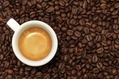 A cup of coffee of espresso on the coffee beans. White cup of coffee of espresso on coffee beans background. . Close-up Royalty Free Stock Photos
