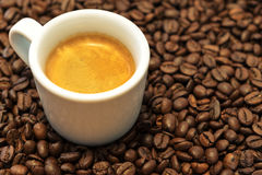 A cup of coffee of espresso on the coffee beans. White cup of coffee of espresso on the rustic coffee beans. Close-up Royalty Free Stock Photos