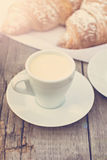 Cup of coffee espresso. A cup of coffee espresso and croissant on the wooden table. Tonned photo Stock Photo