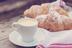 Cup of coffee espresso. A cup of coffee espresso and croissant on the wooden table. Tonned photo Stock Image