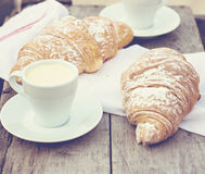 Cup of coffee espresso and croissant. A cup of coffee espresso and croissant on the wooden table. Tonned photo Stock Images