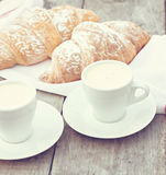 A cup of coffee espresso and croissant. On the wooden table. Tonned photo Royalty Free Stock Photography