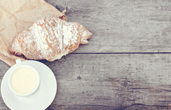 A cup of coffee espresso and croissant. On the wooden table. Tonned photo Stock Photography
