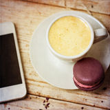 A cup of coffee espresso, macaroon. And a telephone. Toned photo Royalty Free Stock Photo