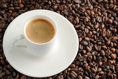 cup of coffee espresso and plate on coffee beans background Royalty Free Stock Images