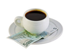 Cup of coffee in the euro money. Isolated on white Royalty Free Stock Photos