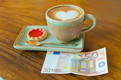 Cup of coffee and euro note.  Stock Image