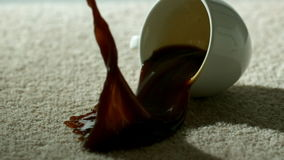 Cup of coffee falling and spilling over carpet. In slow motion stock footage