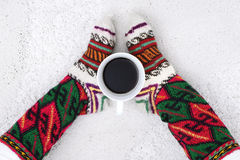 Cup of coffee and female feet with socks on a white carpet, Royalty Free Stock Images