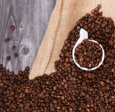 Cup of coffee filled with coffee beans against wooden background Royalty Free Stock Images
