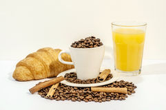 Cup of coffee filled with coffee beans with croissants, cinnamon stick Stock Photography