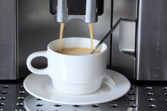 Cup of coffee. Cup filled with freshly brewed coffee from the coffee machine royalty free stock photos