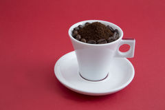 Cup of coffee. A cup filled with ground coffee and coffee beans royalty free stock image