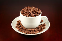 Cup of coffee filled up with coffee beans Royalty Free Stock Photography