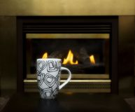 Cup of coffee by fireplace Stock Photo