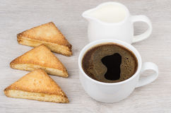Cup of coffee, flaky cookies and jug milk on table Royalty Free Stock Photos