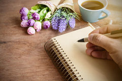 Cup of coffee with flower and blank notebook on wooden table Royalty Free Stock Photos
