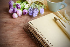 Cup of coffee with flower and blank notebook on wooden table Stock Photography