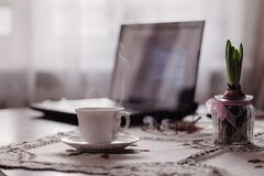 a cup of coffee, a flower and a laptop Stock Image