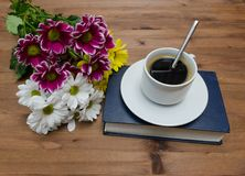 Cup of coffee with flowers and book Stock Image