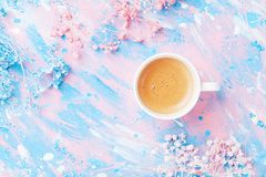 Cup of coffee and flowers on colorful table top view. Flat lay style. Creative breakfast for Woman day. Punchy pastel. royalty free stock photography