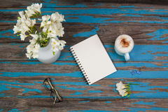 Cup of coffee, flowers in flowerpot, notepad and spectacles placed together Stock Photography