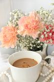 A cup of coffee and flowers on a light background, wishes of good morning and good day, a cozy home. Light and tender spring flowers and coffee with milk on a royalty free stock photo