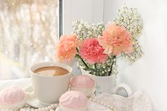 A cup of coffee and flowers on a light background, wishes of good morning and good day, a cozy home. Light and tender spring flowers and coffee with milk on a stock image