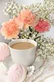 A cup of coffee and flowers on a light background, wishes of good morning and good day, a cozy home. Light and tender spring flowers and coffee with milk on a royalty free stock photography