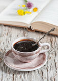 Cup of coffee and flowers on open book Stock Photography