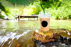Cup of coffee with flowing water in stream Stock Images